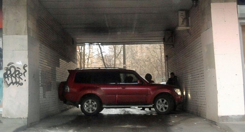 SUV stuck perfectly tight between the walls of the narrow archway