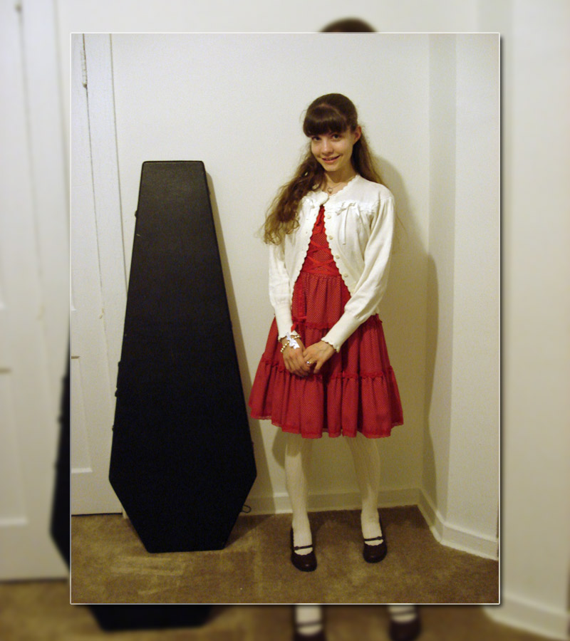 The girl is modeling by the small coffin