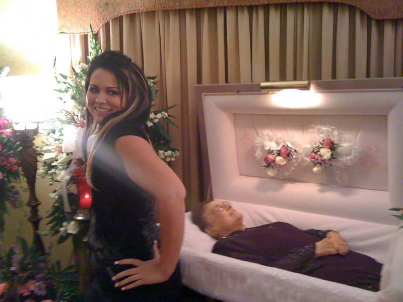 The girl is modeling by the coffin of her grandma