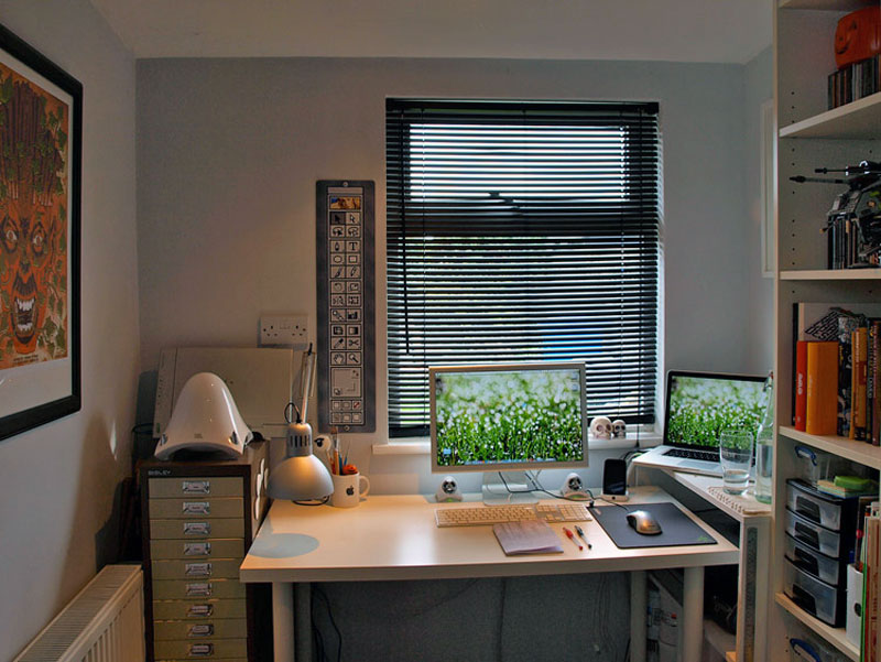 15. Simple and convenient Mac setup with the Adobe Illustrator painting on the wall next to the window