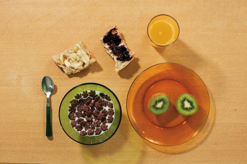 Breakfast on a weekday: kiwi, a baguette with butter and blackberry jam, cereal with milk and freshly orange juice.